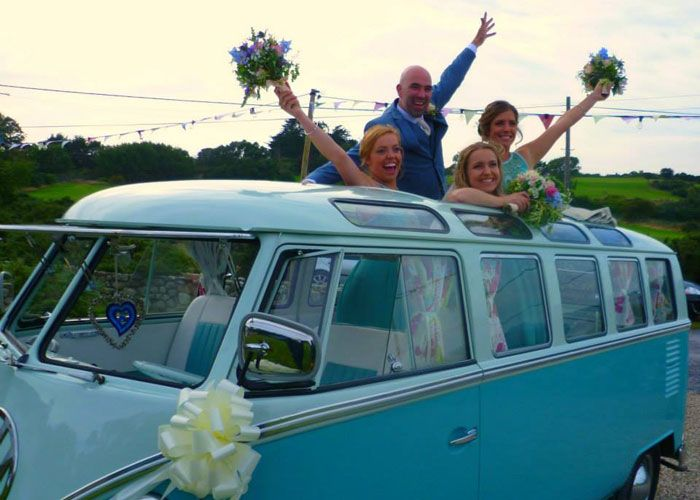 Wedding guests looking out of VW Campervan roof window